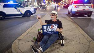 """Enman sitter på en refuge med ett vinglas i handen. I andra handen håller han en skylt med texten """"Biden Harris""""."""