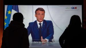 Två personer ser på en tv-skärm där Frankrikes president Emmanuel Macron håller tal.