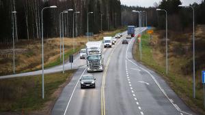 Personbilar och långtradare på landsväg.