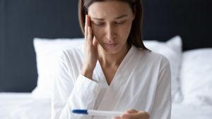 Kvinna ser på graviditetstest och håller sig för pannan