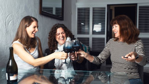 Tre skrattande kvinnor skålar i rödvin