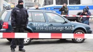 """En polis står framför en bil som målats med texten """"Stoppa globaliseringspolitiken""""."""