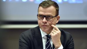 En medelålders man i kostym och glasögon ser fundersam ut.