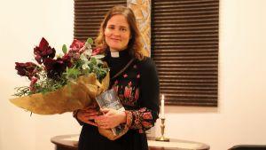En kvinnlig präst står med en blombukett och en bok i famnen.
