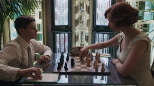 En pojke och en ung kvinna spelar schack.