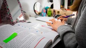 En ung flicka studerar på distans. Hon har framför sig en bok på ett skrivbord.