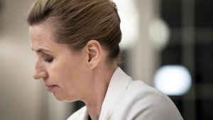 Danmarks statsminister Mette Fredriksen i profil i vit kavaj. Hon ser nedåt. Bilden är från den 29 oktober.
