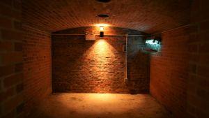 Tegelvägg i källaren som är upplyst av lampor