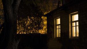 Upplysta fönster i hus på natten