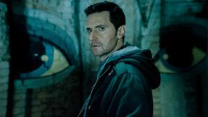 Mies tummassa kuvassa taustalla graffitimaalaus.