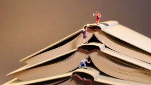 Pieniä ihmishahmoja kiipeilemässä kirjapinon päälle