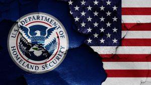 Det amerikanska inrikessäkerhetsministeriet flagga avtecknad på en krackelerad vägg.