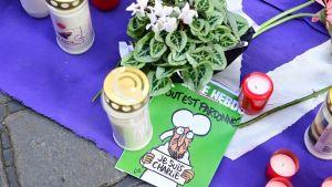 Blommor, gravljus och en karikatyr av profeten Mohammed placerade på en filt