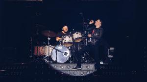 En manlig sångare och en manlig trummis på en scen, upplysta av en strålkastare.