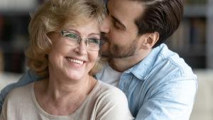 äldre blond kvinna omfamnas av yngre mörkhårig man