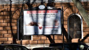 En affisch med italienska slagord mot abortpiller och en bild på en liggande kvinna på en husvägg.