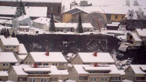 Förstörda hus ligger nere i kratern efter jordskredet.