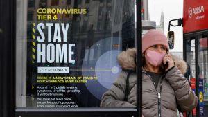 En kvinna med munskydd på sig i London. Hon står bredvid en skylt som uppmanar britterna att stanna hemma och följa de rådande coronarestriktionerna.