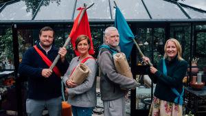 Micke Björklund, Maria Sundblom Lindberg, Pata Degerman och Sofia Torvalds står på rad som två Robinson-lag med en röd respektive blå flagga fastknutna på käppar.