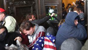 Demonstranterna framför ett krossat fönster