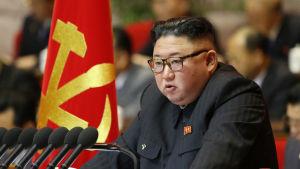 Nordkoreas ledare Kim Jong-Un talar. I Bakgrunden syns Nordkoreas flagga