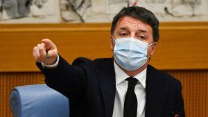 Matteo Renzi bär munskydd och pekar finger.