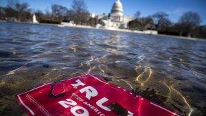 Ett plakat från president Trumps valkampanj skvalpar i vattnet. Kongressen i bakgrunden.
