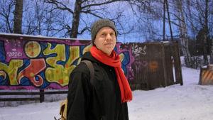 Man i svart jacka och röd halsduk står framför ett snöigt staket.