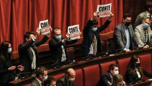 Italiens premiärminister Giuseppe Conti talar till underhuset 18.1.2021. Parlamentariker visar upp plakat med texten Conti, avgå!