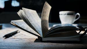 En kaffekopp och en uppslagen anteckningsbok på ett bord.