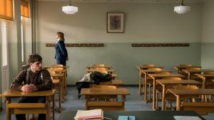 Erik (Jonas Dassler) istuu ainoana oppilaana luokassa. Taustalla opettaja katsoo ulos ikkunasta.
