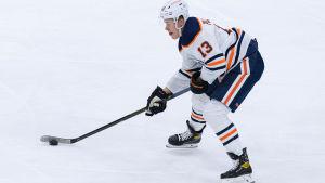 Jesse Puljujärvi för fram pucken på isen, iklädd Edmonton Oilers vita speldräkt.