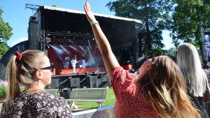 En festivalbesökare sträcker upp ena handen mot himlen och njuter av musik som kommer från en scen utomhus.