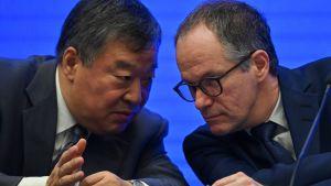 Liang Wannian (till vänster) talar med Peter Ben Embarek (till höger) under en presskonferens 9.2.2021