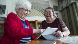 Kaksi mummoa käyttää tablettia kotona