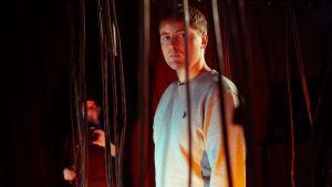 En ung skådespelare står mellan elledningar som hänger ner från taket.