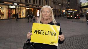 """Tiina Jauhiainen med en skylt där det står """"Befria Latifa"""""""