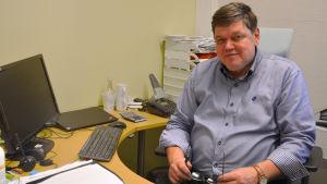 En man som sitter vid ett skrivbord.