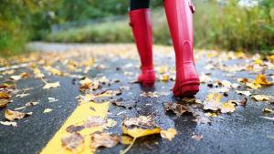 Närbild på fötter iklädda röda gummistövlar