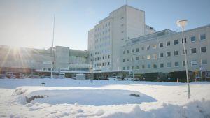 Ljus byggnad i flera våningar, i förgrunden snö på marken.