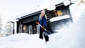 Nainen mustan hirsitalon edessä lapioimassa lunta.