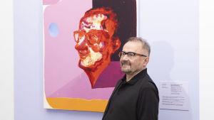 Konstsamlaren Seppo Fränti bredvid Jussi Gomans verk Seppo i ett av utställningsrummen på utställningen Hullu Rakkaus där delar av Fräntis donerade konstsamling ställdes ut.