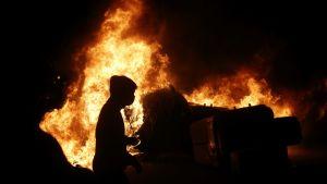 Siluetten av en demonstrant syns framför en brinnande barrikad