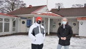 Två män i munskydd fram för ett hus.