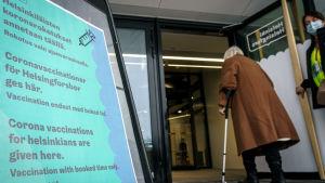 En person på väg in i en coronavaccinatonslokal. Utanför en skylt med text på tre språk om vaccinationslokalen.