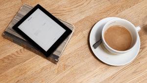 En läsplatta ligger på en bok bredvid en kopp kaffe.
