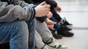 Sjundeklassare sitter i en skolkorridor.