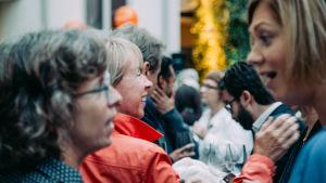 Flera personer minglar och pratar med varandra på en informell sammankomst i samband med en konferens.