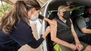 """En kvinna vaccineras på en """"drive-in-vaccineringsplats"""" i Brasilia 10.3.2021"""