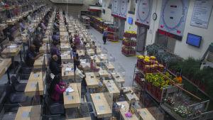 Människor sitter vid bord framför stora lass av blommor.